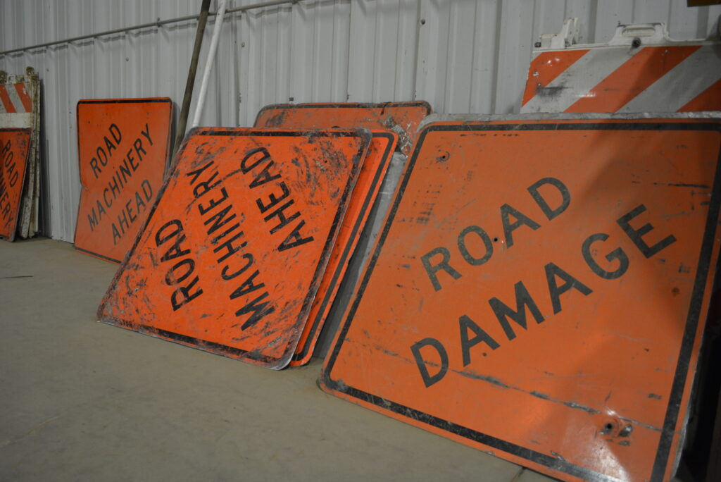 Department of Public Works orange sign that reads Road Damage and Road Machinery Ahead